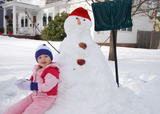Eva seated by snowman