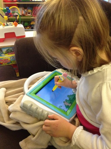 Eva writing her letters with the iLearn Learning Tablet