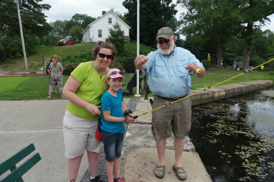 Eva catching a fish with Allison and Uncle Howard