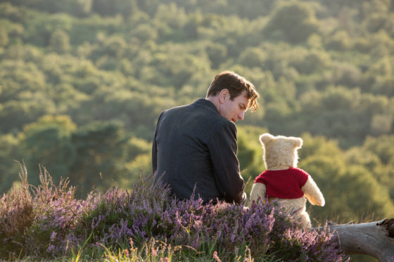 Christopher Robin and Pooh sit on a Log